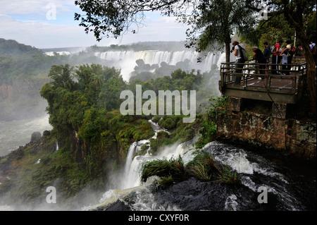 Les touristes sur une passerelle, chutes d'Iguacu Falls ou au patrimoine mondial de l'UNESCO, à la frontière du Banque D'Images