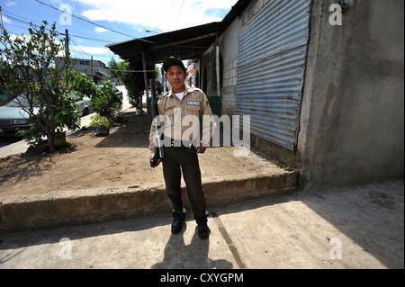 Jeune homme tenant un grand fusil, gardien de sécurité d'une entreprise de camionnage, Lomas de Santa Faz slum, Banque D'Images