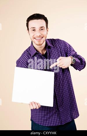 Jeune homme en montrant une carte vierge dans sa main Banque D'Images