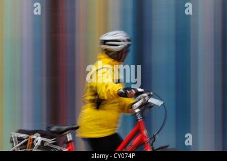 Une femelle avec le vélo touristique passant le Tour Moretti à l'Esplanade du général de Gaulle à la défense, Paris Banque D'Images
