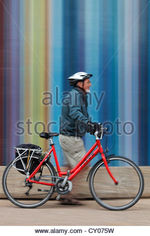 Un touriste à vélo passant Tour Moretti à l'Esplanade du général de Gaulle à la défense, Paris Banque D'Images