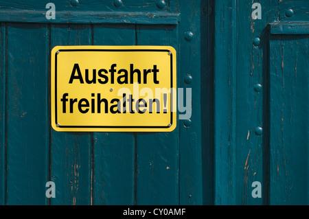 Lettrage signe 'Ausfahrt freihalten', l'allemand pour l'entrée de 'garder' claire, sur une porte en bois vert, PublicGround Banque D'Images