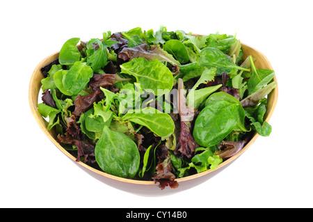 Un bol en bois plein d'un assortiment de légumes verts, y compris, les épinards, roquette, et romaine. Format horizontal Banque D'Images