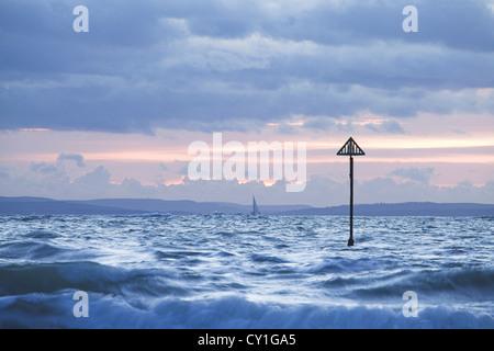 Sunset surf avec petit bateau à voile à distance Banque D'Images