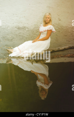 Une femme dans une robe blanche à pois est assis sur une malle près d'un étang Banque D'Images