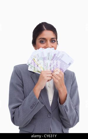 Femme entrepreneur cachant son visage derrière des billets de banque Banque D'Images