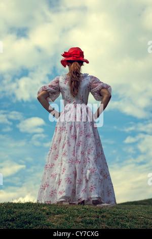 Une femme dans une robe de la flore et une red hat est exécuté sur un pré Banque D'Images