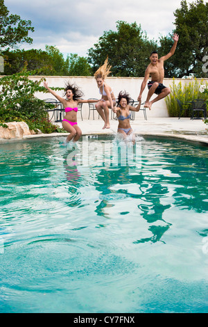 Groupe de 4 adolescents jumping into swimming pool Banque D'Images