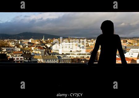 Une jeune femme regarde par une fenêtre sur une ville européenne (Oslo, Norvège). Banque D'Images
