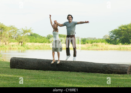 Jeune couple Jumping off log in park Banque D'Images