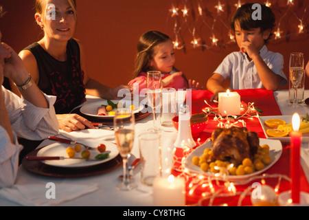 Famille rassemblée autour de la table de dîner de Noël Banque D'Images