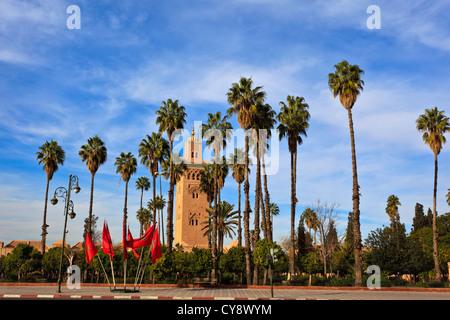De grands palmiers et de drapeaux marocains pour mosquée et minaret à Marrakech. Banque D'Images
