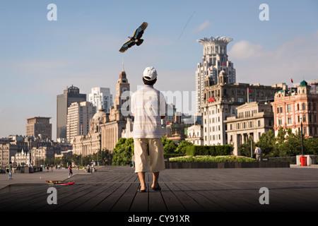 Un homme vole un cerf-volant tôt le matin sur le Bund contre les toits de Shanghai, Chine moderne Banque D'Images