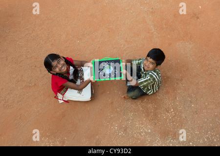 Village indien fille et garçon AVEC UN SEUL MONDE écrit sur un tableau noir dans un village de l'Inde rurale. L'Andhra Banque D'Images