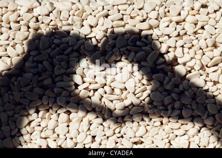 L'ombre de la main en forme de coeur sur les cailloux ovales Banque D'Images