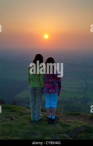 Deux jeunes filles regardant le coucher du soleil depuis le sommet de la colline Wrekin Shropshire en Angleterre Banque D'Images