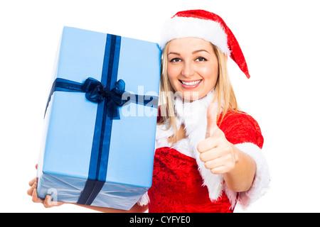 Jeune femme heureuse à Noël le costume holding big blue boîte cadeau et gesticulant thumb up, isolé sur fond blanc. Banque D'Images
