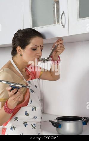 Soupe dégustation femme dans la cuisine Banque D'Images