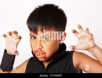 Garçon avec des fausses dents et du sang autour de sa bouche habillés pour Halloween Banque D'Images