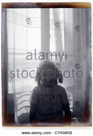 Vitre d'image de jeune fille en face de la fenêtre 1930 Banque D'Images