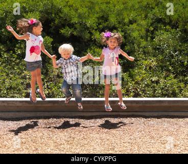 Les enfants sauter ensemble dans park Banque D'Images