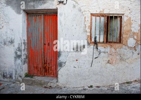 Métal rouge porte et fenêtre barrée sur un mur peint peeling, Andalousie, Espagne Banque D'Images