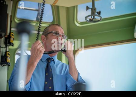 Le capitaine du remorqueur en conversation sur talkie walkie Banque D'Images
