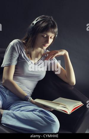 Une jeune femme est assise sur un canapé lit un livre et écouter de la musique à travers une paire d'écouteurs Banque D'Images