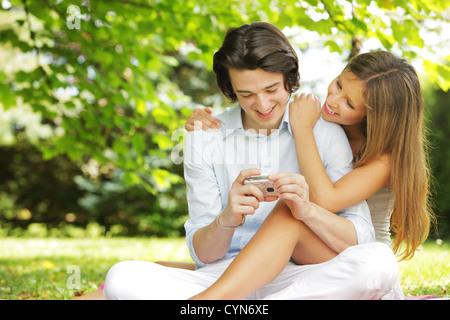 Un couple d'amants, voir les photos sur l'écran de leur appareil photo compact Banque D'Images