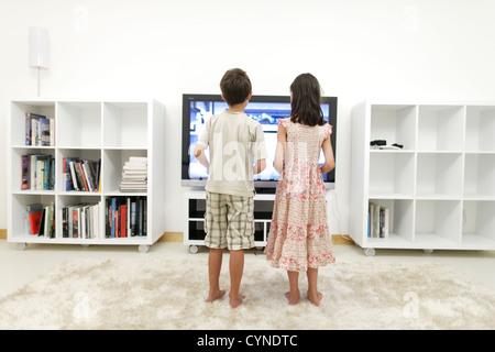 Garçon et fille jouer à des jeux vidéo sur grand écran 55 pouces à la télévision en salle blanche Banque D'Images