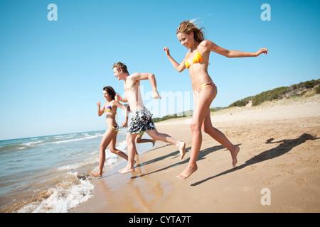 Groupe de jeunes gens qui couraient dans la mer Banque D'Images