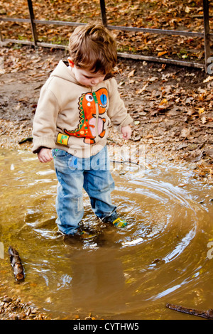 Un jeune garçon les éclaboussures et joue dans une flaque boueuse dans la campagne Banque D'Images