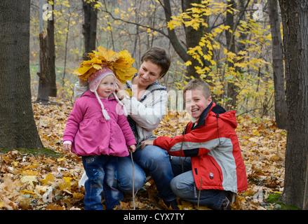 La famille joue à l'automne woods Banque D'Images