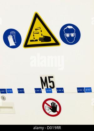 Divers autocollants d'avertissement, des gants industriels nécessaires, les fluides corrosifs danger, protection Banque D'Images