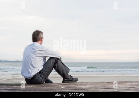 Pensive businessman sitting at the sea Banque D'Images