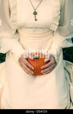 Une femme dans une robe victorienne est assis sur l'herbe et tenant une citrouille sur ses genoux Banque D'Images