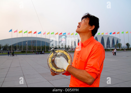 Pudong District Shanghai Chine Xin Oriental Sports Center Asian man kite flyer flying hobby roue ligne du tambour Banque D'Images