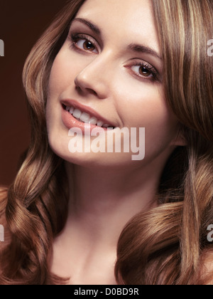 Portrait of a smiling young woman avec de beaux cheveux bruns et points saillants Banque D'Images