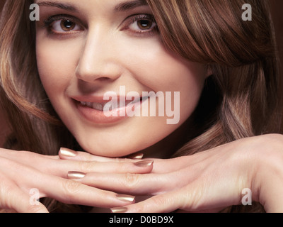 Closeup portrait of a beautiful smiling young woman on her hands Banque D'Images