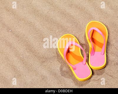Paire de tongs orange sur fond de sable de plage Banque D'Images