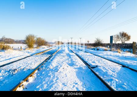 Neige de l'hiver sur des rails de chemin de fer fonctionnant en ligne droite à travers la bretagne campagne, England, Banque D'Images