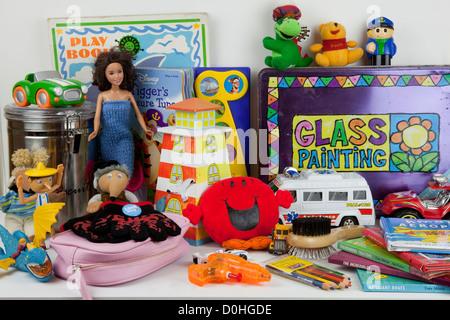 Un assortiment de jouets pour enfants sur la tablette voitures miniatures ours livres gants Banque D'Images