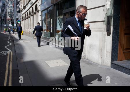 Un homme marche dans une rue de boire du café.