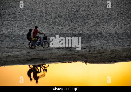 VIENTIANE, Laos - Deux jeunes garçons sur un vélo s'arrêter pour regarder le coucher du soleil. sur un banc dans Banque D'Images