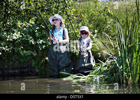 Les petites filles de l'été à la pêche sur le lac Banque D'Images