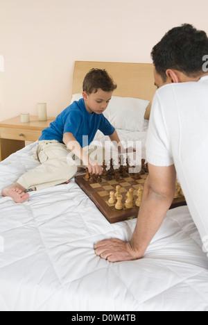 L'homme et son fils jouer aux échecs sur le lit Banque D'Images