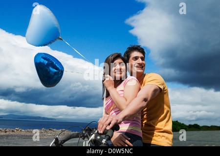 Couple riding a bicycle dans un jardin le long d'une côte Banque D'Images