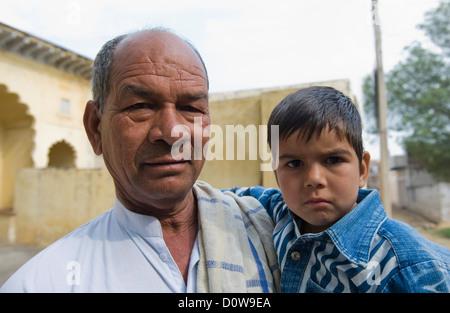 Portrait d'un homme portant son petit-fils, Hasanpur, Haryana, Inde Banque D'Images