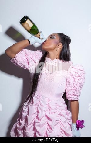 Les jeunes portant robe de bal et de boire une bouteille de champagne Banque D'Images