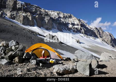Femme se lit dans sa tente au camp l'un sur l'Aconcagua dans la cordillère des Andes, dans la province de Mendoza, Argentine